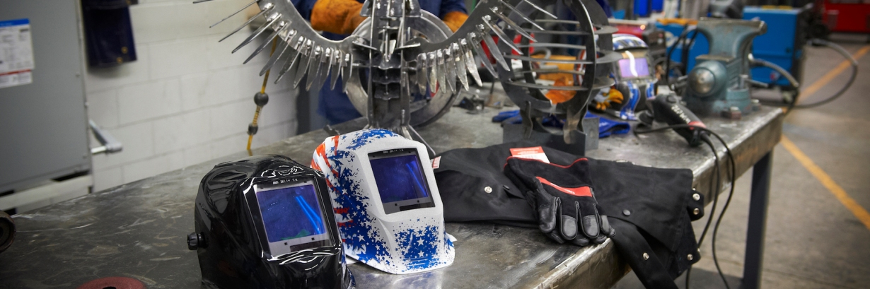 Two welding helmets sitting next to some welding gloves on a metal table.